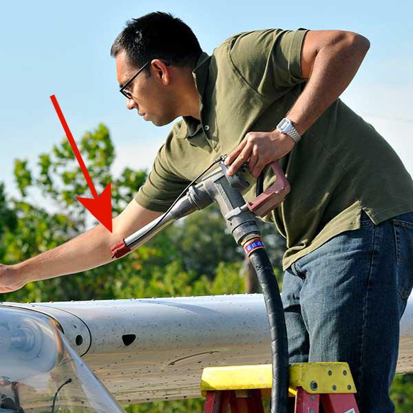 pilot places fuel cap on nozzle when done fueling