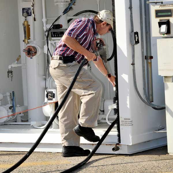 pilot carefully winds fuel hose back