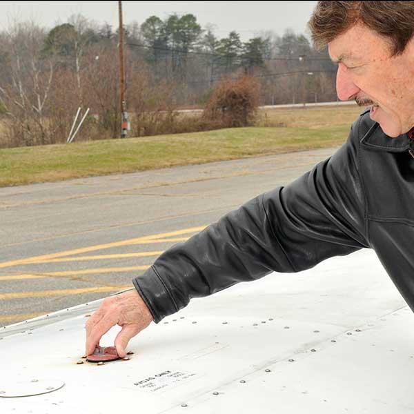 man checking aircraft fuel cap