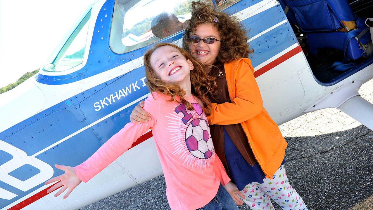 Two young ladies posing by a Cessna Skyhawk Aircraft at a Young Eagles Day at Tipton Airport