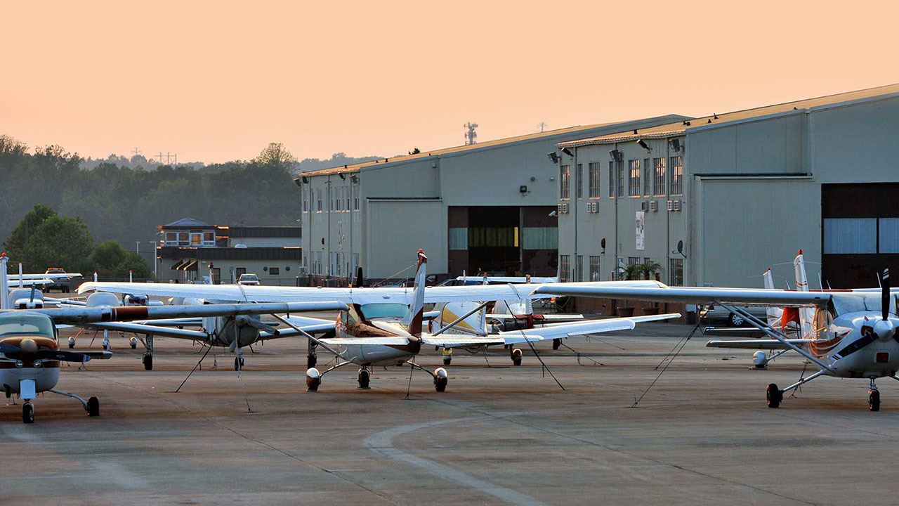 Tipton Airport at day break with planes tied down by hangars